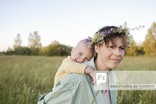 Thoughtful woman piggybacking son during sunny day