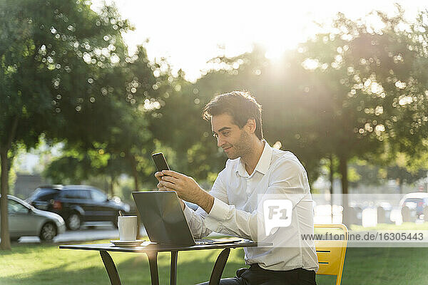 Businessman with laptop on table using smart phone while sitting at sidewalk cafe during sunny day