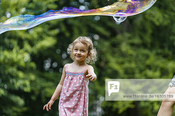 Smiling girl looking at bubble while standing at park