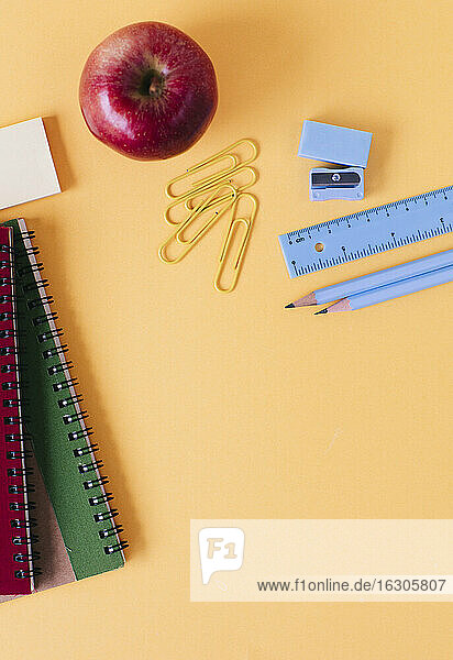 School supplies with fresh apple on yellow table