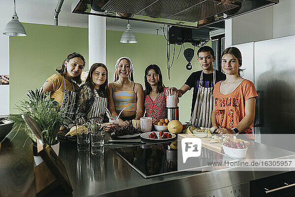 Group of teenagers standing in kitchen  preparing smoothies with a blender