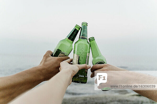 Hands of three friends making celebratory toast with beer bottles
