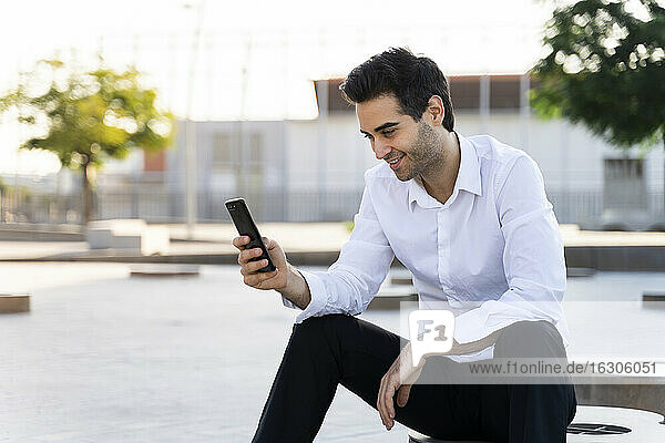 Handsome businessman using smart phone sitting against sky in city