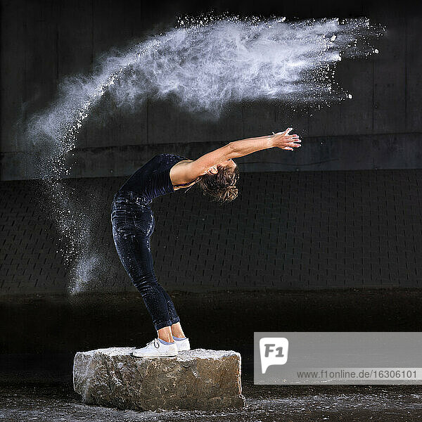 Woman dancing with flour against wall