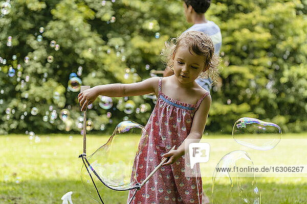 Cute baby girl making bubble with brother in background at park