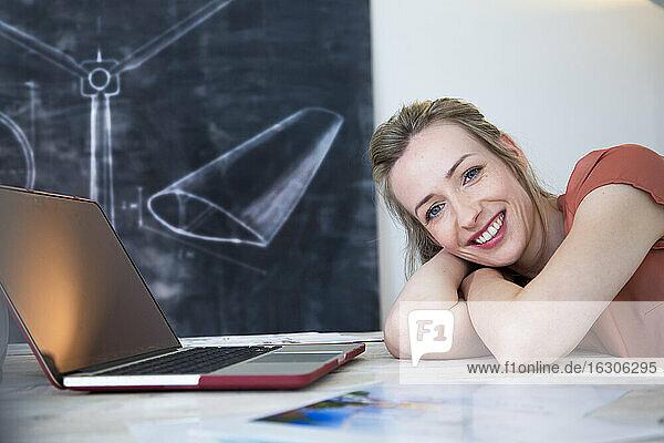 Portrait of happy woman leaning on desk in office