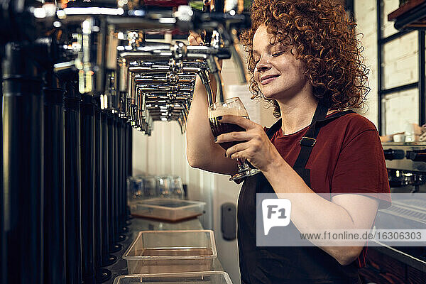 Female barkeeper tapping beer in a pub