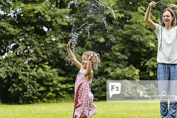 Girl exploding bubble while enjoying at public park