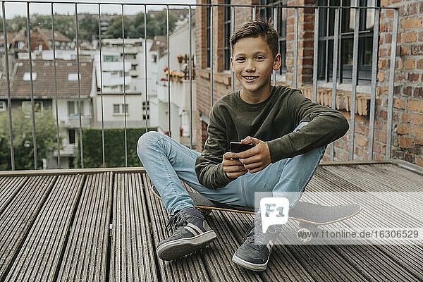 Smiling boy using smart phone while sitting on skateboard against railing