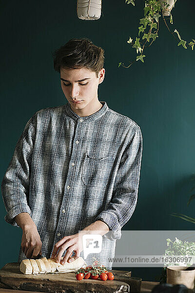 Handsome young man cutting fresh homemade bread by cherry tomtoes on board in kitchen