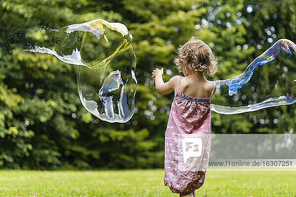Girl playing with bubbles at park