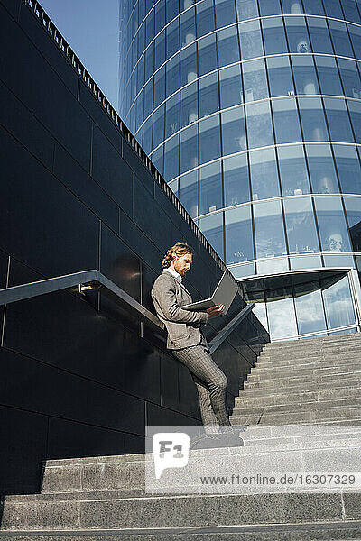 Businessman using laptop while leaning against wall on staircase in downtown during sunny day