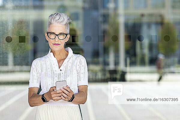 Senior woman using smart phone while standing against glass window on street