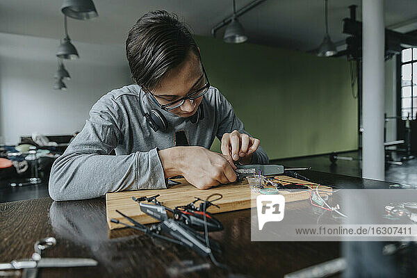 Young man tinkering with soldering iron at home
