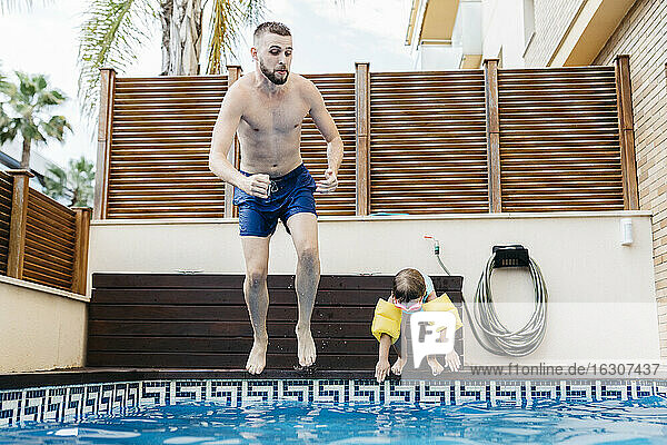 Little girl jumping with uncle into swimming pool