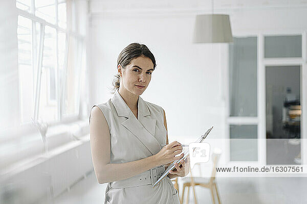 Businesswoman holding notepad while standing at office