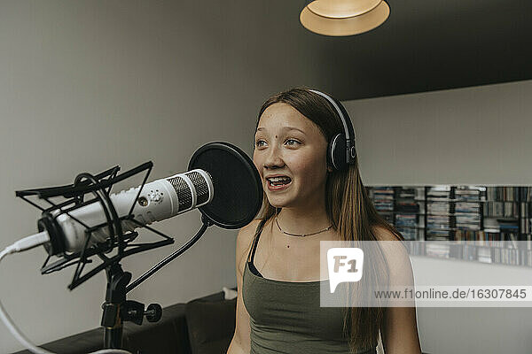 Teenage girl singing over microphone while standing against wall in recording studio