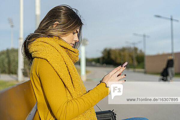 Young woman texting through mobile phone while sitting on bench in park