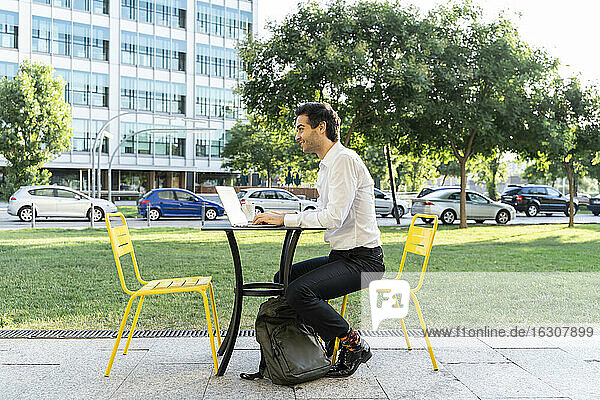 Male entrepreneur using laptop on table while sitting at sidewalk cafe