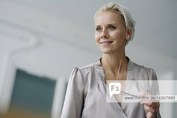 Close-up of thoughtful businesswoman holding eyeglasses while standing in office