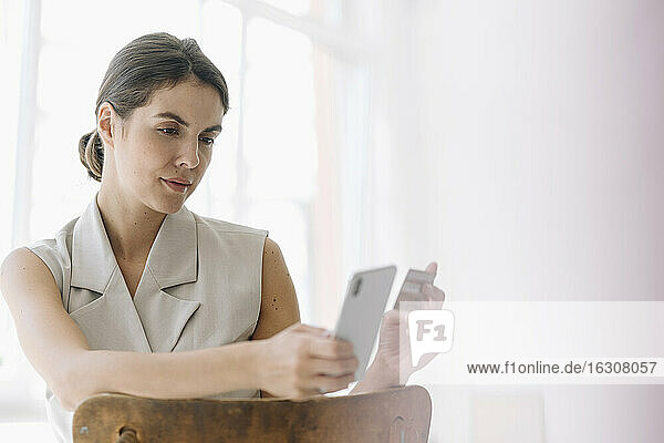 Businesswoman holding credit card while using mobile phone at office