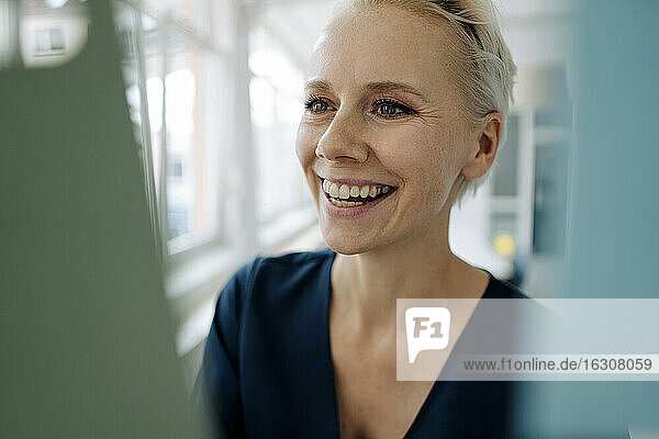 Close-up of smiling businesswoman looking at window in office