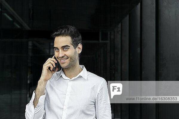 Smiling male professional talking over smart phone in office