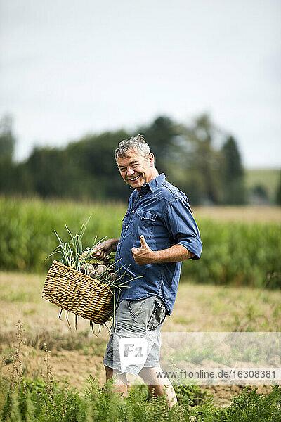 Man showing thumbs up while walking at farm
