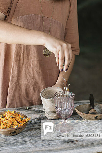 Midsection of woman preparing fresh herbal tea in glass