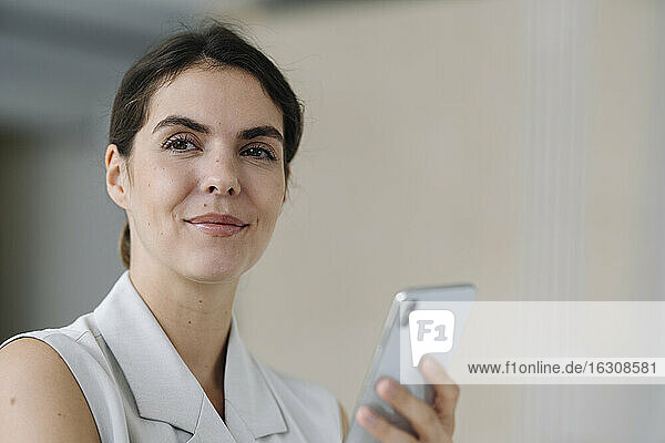 Smiling woman holding mobile phone while standing at office