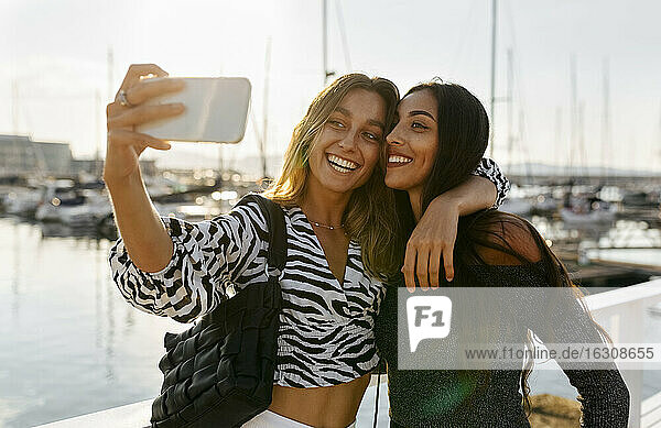 Friends taking selfie with phone while standing at harbor