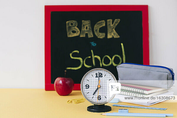 Close-up of alarm clock with school supplies and apple on table