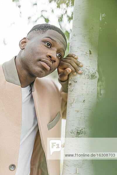 Thoughtful young male leaning on tree