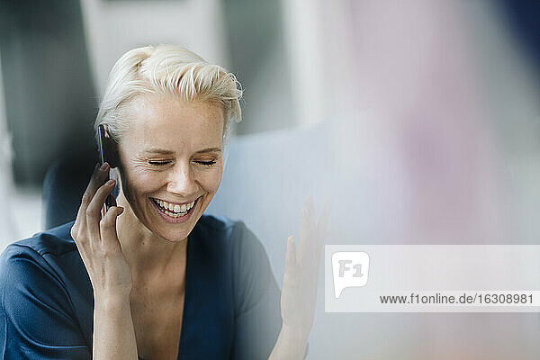 Close-up of cheerful businesswoman with eyes closed talking over smart phone in office