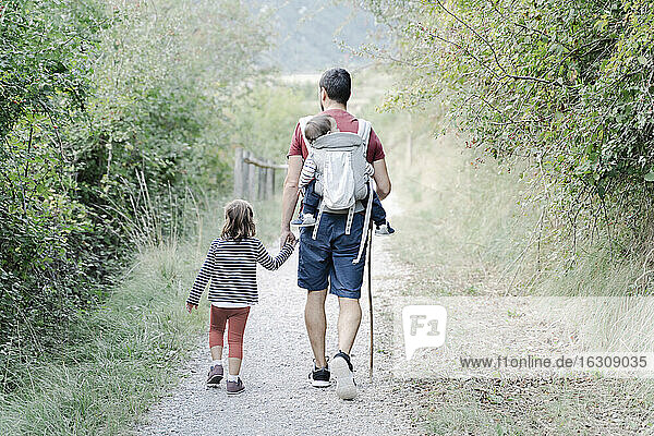 Father hiking with his children  carrying son on back while holding hand of daughter