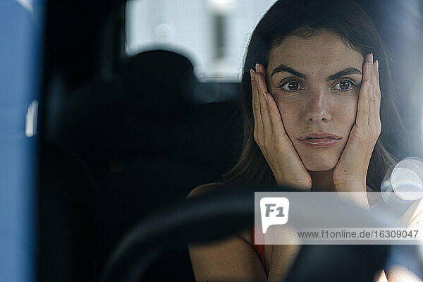 Woman with head in hands getting bored while sitting in car