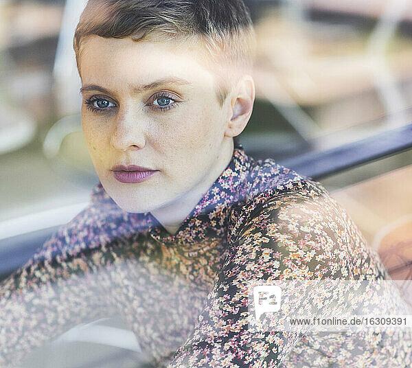 Portrait of a woman behind windowpane