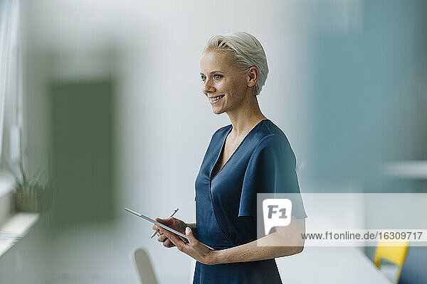 Smiling businesswoman with digital tablet looking away while standing in office