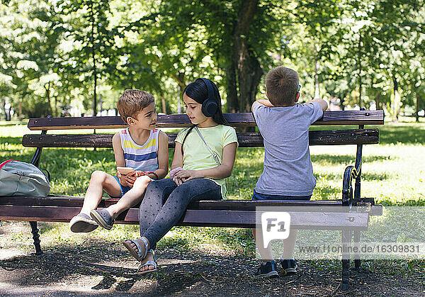 Girl wearing headphones talking to friend in park