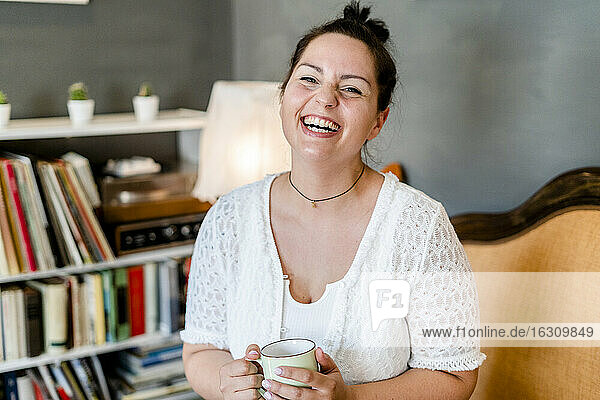 Cheerful voluptuous young woman holding coffee mug while sitting in cafe