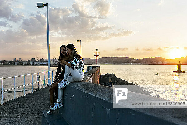 Friends using phone while sitting on retaining wall at promenade during sunset