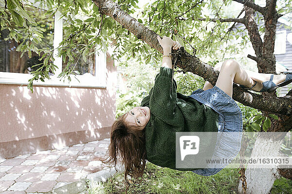 Cute girl hanging from tree branch in back yard