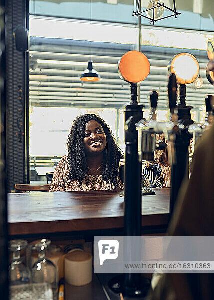 Lächelnde junge Frau am Tresen in einer Kneipe Lächelnde junge Frau am Tresen in einer Kneipe