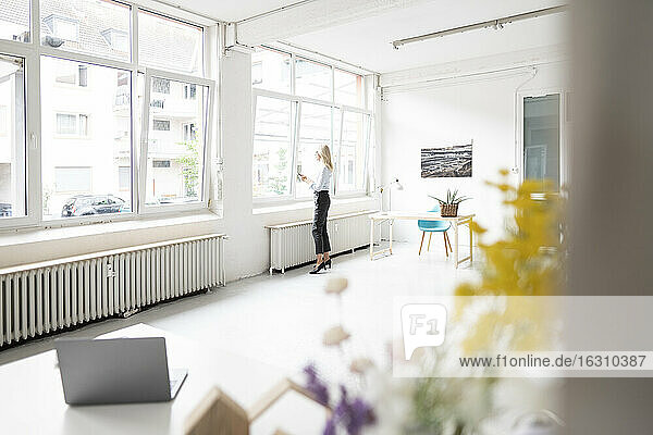 Businesswoman standing by window in home office