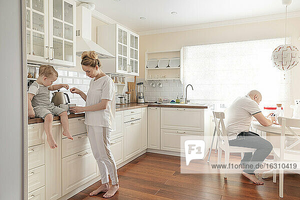 Mother and son preparing tea in kitchen