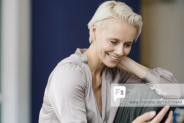 Close-up of smiling female entrepreneur using mobile phone while sitting in office