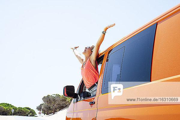 Fröhliche Frau mit ausgestreckten Armen  die sich durch das Fenster aus dem Auto lehnt Fröhliche Frau mit ausgestreckten Armen, die sich durch das Fenster aus dem Auto lehnt