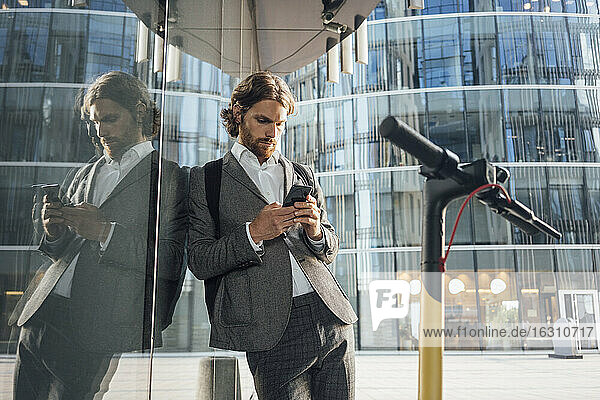 Male entrepreneur using smart phone while leaning on glass by electric push scooter in financial district