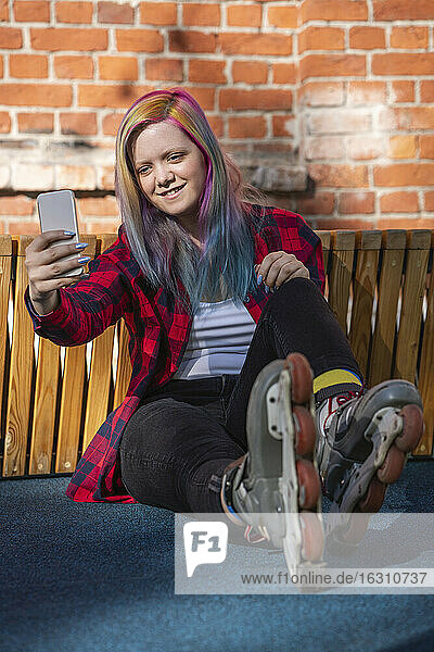 Young woman with dyed hair and roller skates taking a selfie with her smartphone