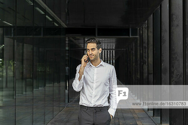 Businessman with hand in pocket talking over smart phone at office